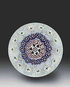 Antique Baccarat close concentric shamrocks and millefiori, with outer spaced concentric ring of 14 moth canes on an upset muslin ground. Circa 1845–55. Diameter 3 inches.