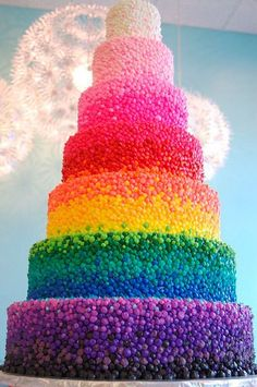 This picture shows a cake with the colours of the rainbow layered out from black all the way to white. This picture vibrant colours with dark colours and light colours.