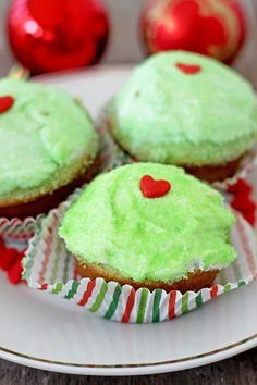 These Easy Grinch Cupcakes start with a cake mix and a box of lime Jello for that perfect Grinchy green.  Topped with frosting, green sanding sugar and a red heart sprinkle, they're perfect for a Grinch viewing party or just a fun Christmas treat that's not a cookie!