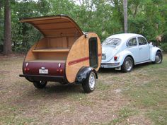 Teardrop Camper with nice woodworking, towed by a bug.
