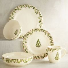 Oh, what fun it is to dine on a special Christmas plate. Our heirloom-worthy Winter's Wonder pattern has all the makings of a family tradition. Crafted of solid ironstone, each piece features a border of holiday greenery and red holly berries. The salad plate, bowls and mug also feature a snow-covered evergreen tree in the center.