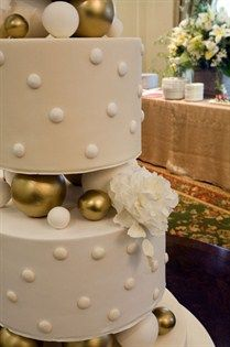 A white sugar peonie rests next to white and gold balls between the layers of this modern wedding cake.
