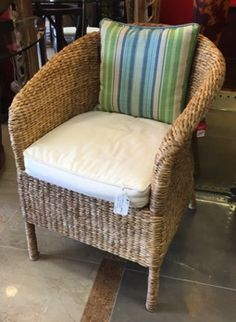 "Crate & Barrel island chair has the perfect tropical look for your guest room or den. Twisted raffia on rattan frame with cotton canvas seat cushion. 27"" x 26"" x 32. Tommy Bahama throw pillow sold separately."