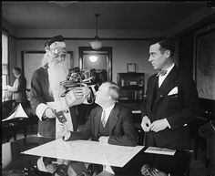 "Blog post: ""Caught Our Eyes: Santa Gets Credentials"" by Barbara Natanson, December 24, 2013. Pictured: Santa Claus receives aeroplane pilot's license from Assistant Secretary of Commerce... / Harris & Ewing. [1927 November or December]. Harris & Ewing Collection, Library of Congress Prints and Photographs Division."