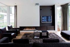 Schellen Architecten: Nijlen.  Interieur living. Strak interieur en toch een beetje landelijk door de haard en de mat.