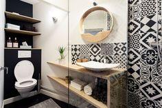 Dans la salle de bains, les carreaux de ciments recouvrent l'espace douche