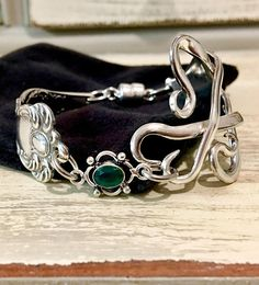 1901 Oxford pattern silverware fork is used to create this one of a kind heirloom bracelet. Embellished with a rough cut Emerald gemstone connector and our magnetic clasp for first class security and easy on and off. Sized for average+ but can be sized up or down if requested.