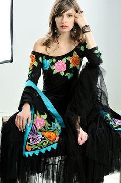 Vestido negro con bordados de colores vivos. Escote importante