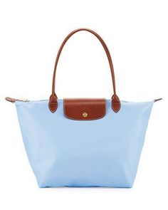 "Longchamp tote in durable, lightweight nylon. Embossed leather trim and pale golden hardware. Rolled top handles, 9"" drop. Zip top with signature racing horse medallion pull. Snap flap at center with race horse embossing. Interior, one open pocket; water-resistant lining. Can be folded into small pouch. 12.3""H x 12""W x 7.5""D; weighs 11.4 oz. ""Le Pliage"" is imported."