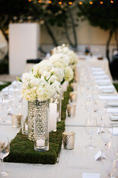 Centerpieces featuring white hydrangea, peonies and orchids with white knob glass and mercury glass