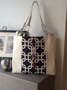 """""""Unsinkable Style!""""  This large bag is a mix of soft white vinyl and crisp navy and white cotton.  The nautical theme continues with partial chain handles, and seashell, seahorse, and anchor charms cascading down the front.  Check out Bobbin My Thread on Facebook to see other designs by Nena."""