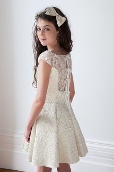 This is our ivory and gold girls bridesmaid dress, the perfect wedding guest outfit for your young lady. With a wedding appropriate ivory and gold colour way, an embossed stylish design and a modern flattering fit, you can't go wrong with such an elegant dress. Your girl will adore the sheer lace fabric insert on the puffed sleeves and to the back of the dress. It fastens with four ties and also has a scooped neckline for added glamour. Fitted bodice and full pleated skirt. Can be worn with…