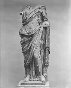 Ionic-This figure wears three layers of clothing: a sleeved chiton visible below the neck, which is tied with a looped knot at the waist; a second chiton or peplos, fastened on both shoulders; and a himation (cloak), draped over the left shoulder and the lower part of the body.