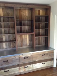 Bookcase After - Entire bookcase covered in reclaimed salvaged vintage wood fencing panels and barn pull handles. The desktop was clad with a sheet of galvanized metal. Thank you San Diego Urban Timber!