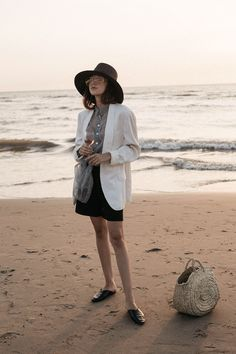 Girl on the beach by the sea during sunset editorial with a glass of rose wine in white masculine blazer organza shirt and straw bag outfit inspiration