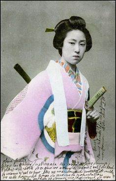 A woman with a katana at her side and a wooden or bamboo shaft of another…