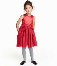 Sleeveless dress in woven fabric with a slight sheen, with buttons down the back. Seam at the waist with a narrow ribbon and floral appliqué, and skirt in a double layer of tulle with a glitter print. Lined.