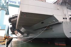 A view up the port side from right aft. The stern configuration is noticeably different from the Nimitz class. The flight deck is much larger aft on both sides  to compensate for the island structure being placed further aft, resulting in enormous overhangs on both sides.