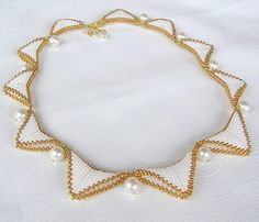 Elegant jewelry!  The necklace is sewn from high quality Japanese seed beads (white) and Czech seed beads Preciosa (gold).  Sharp edges of the triangles are softening white wax pearls.  Length of necklace is 45 cm + 5 cm adjust with pearl. In detail, photographing the surface and in a