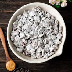 Overhead view of a bowl of the best puppy chow recipe with a spoon full of peanut butter and a bowl full of chocolate chips near it