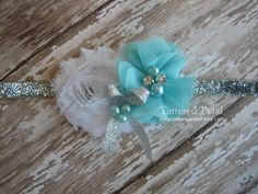 An Elsa-inspired headband. A white shabby chic flower, aqua petite chiffon flower, and glittery silver bow with aqua peal accents. Flowers can be