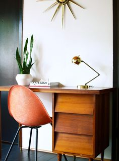 Very simple and clean desk space with a mid-century inspired desk and chair. I love the gold table lamp and the beautiful starburst mirror.