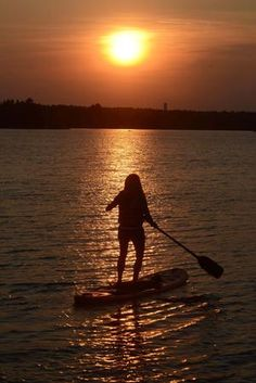 Linda Richard of Bridgewater paddle boards at sunset on Lake Nippenicket in Bridgewater on Wednesday, July 17, 2013. Quincy, MA - The Patriot Ledger