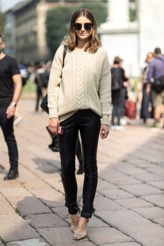 Model off-duty street style fashion: comfy neutral tan sweater with sexy tight leather pants.