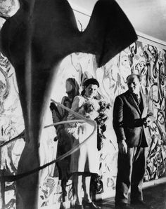 Peggy Guggenheim and Jackson Pollock in front of Pollock's Mural (1943) in the first-floor entrance hall of Guggenheim's residence, 155 East 61st Street, New York, c. 1946. (Other work shown: unidentified David Hare sculpture).