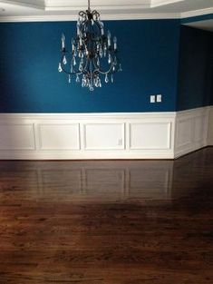 Sherwin Williams Oceanside blue walls; Dining room with dark hardwood floors; Crystal and iron chandelier; 2nd step to the transformation was restaining the floors by laverne