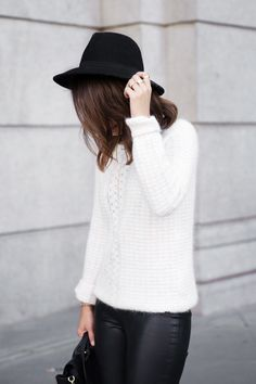 White knit sweater with black leather leggings and a hat to accessorize, hot winter look!
