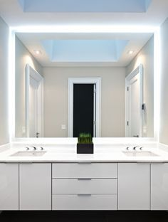 Bathroom Mirrors Lit From Behind modern white bathroom with sliding mirror cabinets | luxe magazine
