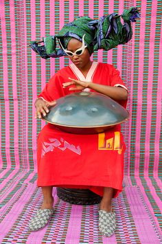 Picture of a seated musician playing the drum in front of a pink and blue textured background -- Hassan Hajjaj