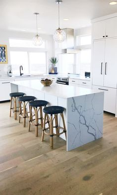 Beach house kitchen with Dal Tile One quartz countertops, Statuary. Light oak floor and modern white cabinets. Aquamarine Beach House, Port Aransas TX.