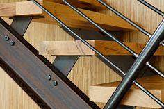 STUDIO-E architecture Fern Ridge House_The open staircase's treads were made from black oak felled and milled on the property; the railing is made from exposed metal beams and bolts..