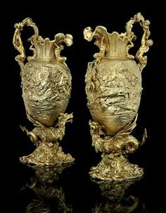 AN IMPORTANT AND MASSIVE PAIR OF GEORGE IV SILVER-GILT EWERS  MARK OF EDWARD FARRELL,   LONDON, 1824, RETAILED BY KENSINGTON LEWIS  Each ovoid, the domed foot cast and chased with rococo scrolls and shells and with the Royal arms of France below a crown three times, on a stem cast as a dragon, the bodies chased with scenes from the Battles of Alexander the Great, with satyr and dragon handles and rocaille necks, the spout supported on a satyr, marked xxx-