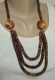 This wonderful necklace has a great design, with the front being a triple strand of coconut wood beads attached to two shellacked shells. The shells are very beautiful, more so than the pictures show.