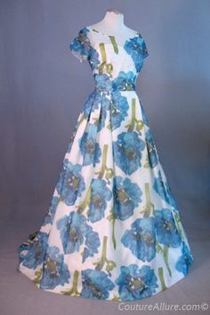 """Vintage 1960s Chiffon Floral Evening Gown W/Train -Fashioned of sheer chiffon w/a large scale blue floral print. Colors are blue, turquoise and green on a white background. Cap sleeved bodice has a bustier style lining that shows through the sheer chiffon. Very full skirt is pleated onto bodice. Skirt is cut 8"""" longer in the back to form a train. Lined completely w/white taffeta."""