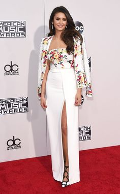 Nina Dobrev from 2015 American Music Awards: Red Carpet Arrivals  We are so not worthy. The Vampire Diaries star is all smiles in a white two-piece ensemble with bright, floral accents.