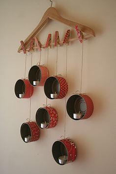 Best translation~empty washed tuna cans,wooden hanger, scrapbook paper,twine,wooden clothes pins. cover cans and pins in paper, glue twine to cans at different lenghts using pins to hang from hanger.  place tea lights in cans. {blog is in Hungarian}