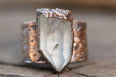 This raw crystal ring is gorgeously organic and rustic. It features one large raw quartz crystal inside of copper. The thick and sturdy band has been hand stamped with an intricate geometric design.    I created the ring with a technique called electroforming. Copper is deposited over the stone over 12-24 hours using electrical currents. It creates a gorgeously organic and hefty piece with a setting that looks like animal skin or something pried right out of the earth. The copper has been…