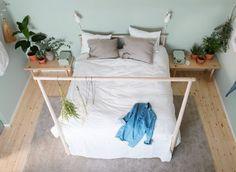 라이트그린 색상의 벽에 밝은 톤의 천연 텍스타일로 꾸민 침대, 낮은 침대협탁, 화분을 조합하여 대칭 구조로 꾸민 침실이에요.