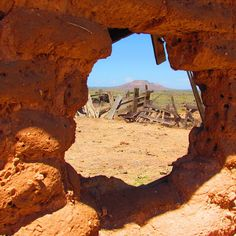 Tucumcari, NM - A view of Tucumcari Mountain from a hole in an old adobe wall of a chicken house.