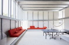 "The main living area, on the home's second floor, was designed with flexibility in mind; its centerpiece is a ping-pong table from Joola. Anton and Débora ""hacked"" several Copa convertible sofas from Serta, removing the legs so they could place the seats directly onto the elevated platform that lines the walls. They also altered Lersta floor lamps from IKEA and wall-mounted them as sconces."
