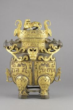 Chinese Gilt Bronze Censer Cast Rhinoceros Heads Beautifully carved, Chinese gilt bronze censer, of ovoid form support on four horse leg-like foot, body carved with gold painted archaistic designs, neck flanked with two rhinoceros heads. Top with chilong and flanked with pair of dragon heads on lid. H: 27 cm, W: 20 cm. Provenance: T. Ng Collection Toronto.