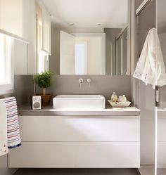 Baño en blanco y gris con grifos empotrados. En el baño