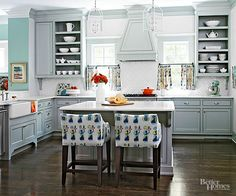 Basic doesn't have to mean boring. The greenish-gray cabinetry and sparkling white backsplash in this cottage kitchen get a lift from funky fabrics. Symmetrical open cabinetry shows off everyday china in different shapes and sizes. The pretty pops of white break up the monochromatic cabinetry.