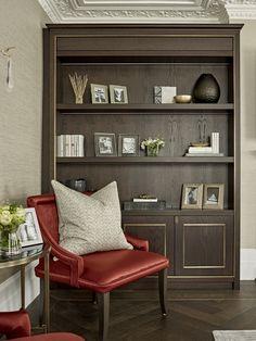 Bespoke joinery in walnut, dark wood, shelving, seating area, red upholstered chairs, crimson, side table, hardwood herringbone flooring.