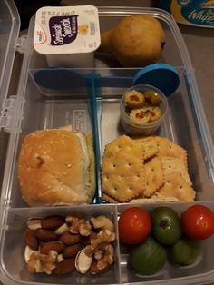 Ham slider, yogurt, fruits, veggies, nuts, stuffed olives and crackers.