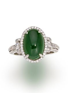 A jadeite jade and diamond ring  centering an oval cabochon jadeite jade, measuring approximately 13.2 x 9.1mm., within a round brilliant-cut diamond surround completed by an openwork diamond-set gallery of heart motif; mounted in eighteen karat white gold;